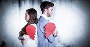 Image composée de la vue de côté de jeunes couples tenant le coeur brisé Photographie stock libre de droits