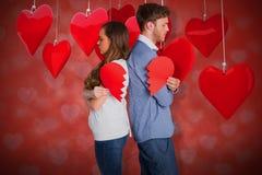 Image composée de la vue de côté de jeunes couples tenant le coeur brisé 3D Images libres de droits