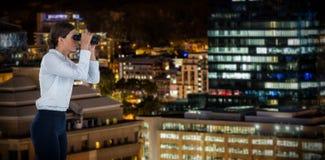 Image composée de la vue de côté de la femme d'affaires regardant par des jumelles Image libre de droits