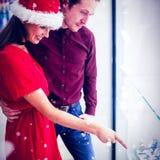 Image composée de la vue de côté des couples dans le vêtement de Noël regardant l'affichage de montre-bracelet Image libre de droits