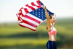 Image composée de la vue de profil de la sportive soulevant un drapeau américain Image stock