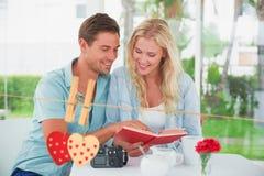 Image composée de livre de lecture mignon de couples de hippie ensemble à la table Image stock