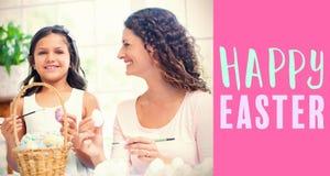 Image composée de mère heureuse et de fille peignant des oeufs de pâques Photos stock