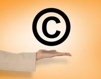 Image composée de main femelle présentant le symbole de copyright Images stock
