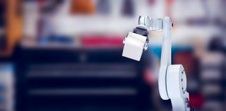 Image composée de main robotique tenant le cube 3d en métal Images stock