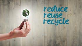 Image composée de main tenant l'ampoule environnementale Photos libres de droits