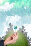 Image composée de main tenant l'ampoule environnementale Photographie stock