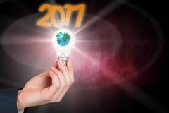 Image composée de main tenant l'ampoule environnementale Images libres de droits