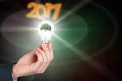 Image composée de main tenant l'ampoule environnementale Photos stock