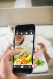 Image composée de main tenant le smartphone Photographie stock libre de droits