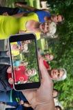 Image composée de main tenant le téléphone portable sur le fond blanc Photo stock