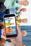 Image composée de main tenant le téléphone portable sur le fond blanc Photos libres de droits