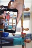Image composée de main tenant le téléphone portable sur le fond blanc Photos stock