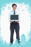 Image composée de marchand de sourire présentant l'écran de son ordinateur portable Images stock