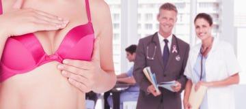 Image composée de mi section de la femme dans le soutien-gorge rose examinant le sein pour assurer la conscience de cancer photographie stock libre de droits