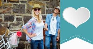 Image composée de mur de briques se tenant prêt de jeunes couples de hanche avec leurs vélos Photos stock