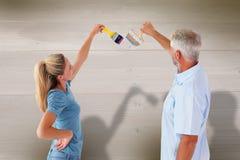 Image composée de mur heureux de peinture de couples avec des pinceaux Photo libre de droits