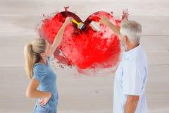 Image composée de mur heureux de peinture de couples avec des pinceaux Photographie stock libre de droits