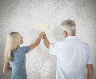 Image composée de mur heureux de peinture de couples avec le rouleau Photographie stock