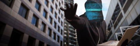 Image composée de pirate informatique tenant l'ordinateur portable tout en faisant des gestes Photographie stock