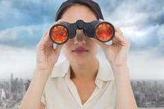 Image composée de plan rapproché d'une femme d'affaires regardant par des jumelles Photographie stock