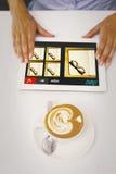 Image composée de plan rapproché de comprimé numérique et de café sur la table Image stock