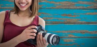 Image composée de portrait de la belle femme de sourire tenant l'appareil photo numérique Images libres de droits