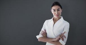 Image composée de portrait des bras debout de belle femme d'affaires croisés Image stock