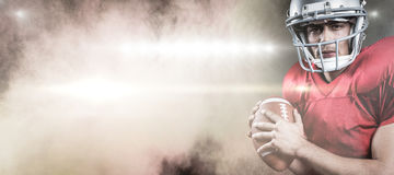 Image composée de portrait du joueur de football américain sérieux tenant la boule Image libre de droits