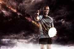 Image composée de portrait du joueur sûr de rugby souriant et montrant des pouces  Images stock