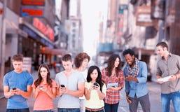 Image composée de quatre personnes se tenant près de l'un l'autre et textotant à leurs téléphones Photo stock