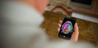 Image composée de roue de la fortune colorée sur l'affichage mobile Photos libres de droits