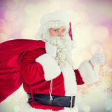 Image composée de Santa positive avec son sac et pouces  Photos libres de droits