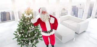 Image composée de Santa tenant un sac et une ondulation Photographie stock libre de droits