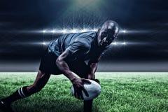 Image composée de sportif déterminé semblant partie tout en jouant le rugby et le 3d Photo stock