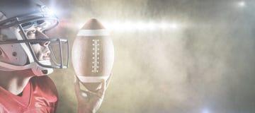 Image composée de sportif recherchant tout en tenant le football américain Image libre de droits