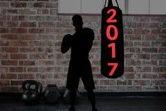 Image composée de 2017 sur le sac de sable et la silhouette du boxeur Images stock