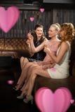Image composée de trois amis féminins ayant la tequila dans la barre Image libre de droits