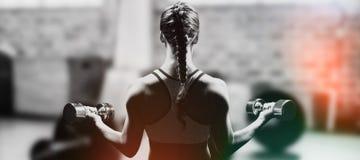 Image composée de vue arrière des haltères de levage de femme tressée de cheveux images stock