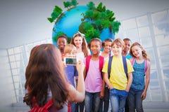 Image composée des élèves mignons à l'aide du téléphone portable Photographie stock