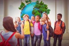 Image composée des élèves mignons à l'aide du téléphone portable Photographie stock libre de droits