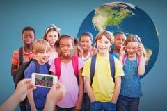 Image composée des élèves mignons à l'aide du téléphone portable Photos stock
