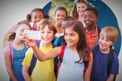 Image composée des élèves mignons à l'aide du téléphone portable Photos libres de droits