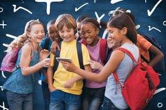 Image composée des élèves mignons à l'aide du téléphone portable Images libres de droits