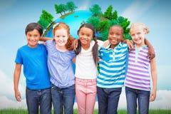 Image composée des élèves mignons souriant à l'appareil-photo dans la salle de classe Photo libre de droits