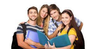 Image composée des étudiants tenant des dossiers au couloir d'université Images stock