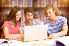 Image composée des étudiants universitaires à l'aide de l'ordinateur portable dans la bibliothèque Photographie stock