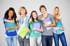 Image composée des étudiants universitaires heureux faisant des gestes des pouces  Image stock