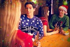 Image composée des amis ayant des bières par la table pendant le Noël Photo stock