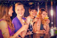 Image composée des amis ayant le verre du cocktail dans la barre Images stock